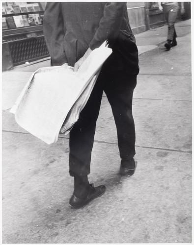 Man walking with newspaper behind his back.jpg