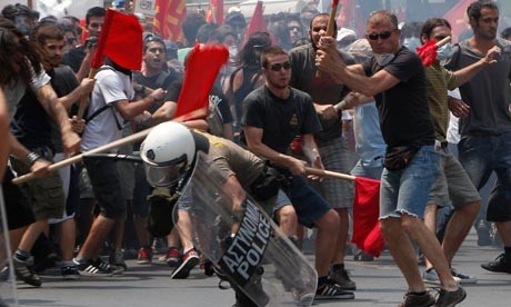 Rioters beat a policeman during a rally against go