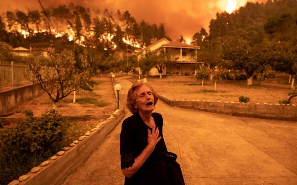 An elderly resident reacts as a wildfire approache