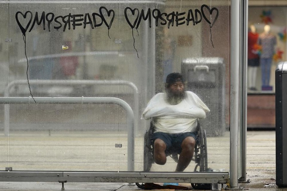 A man takes cover in a bus stop shelter as Hurrica