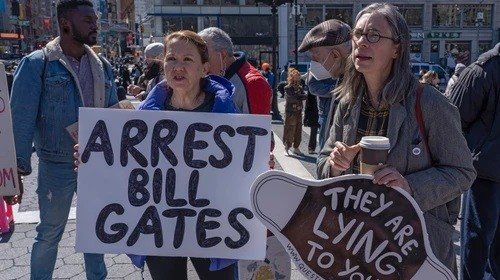 Protesters hold placards saying arrest Bill Gates