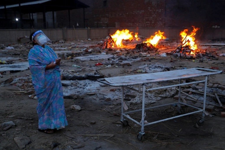 A woman cries during the cremation of her husband,