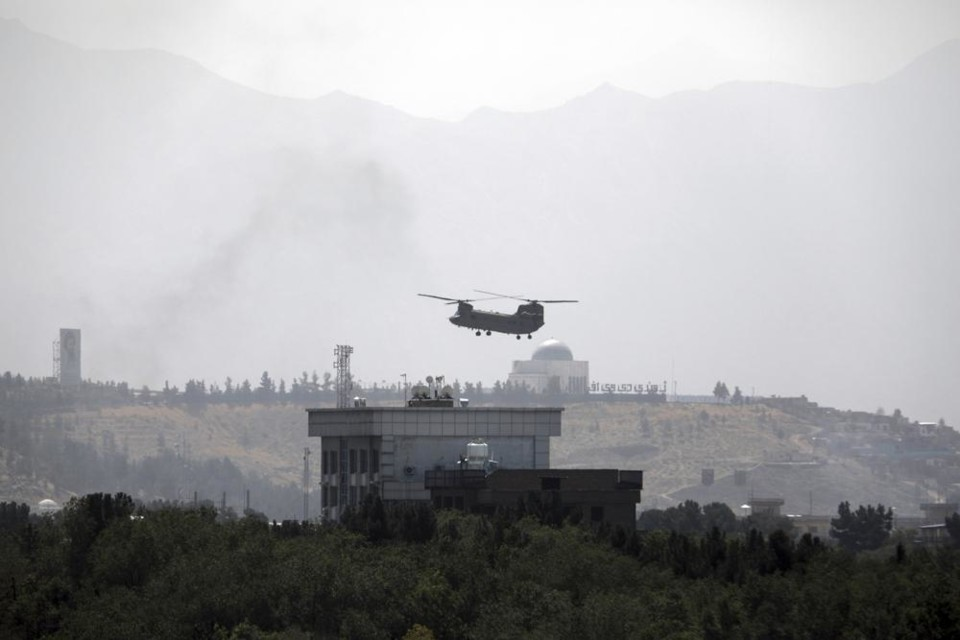 A U.S. Chinook helicopter flies over the U.S. Emba