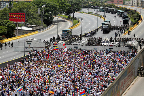 Demonstrators gather in front of the police as the