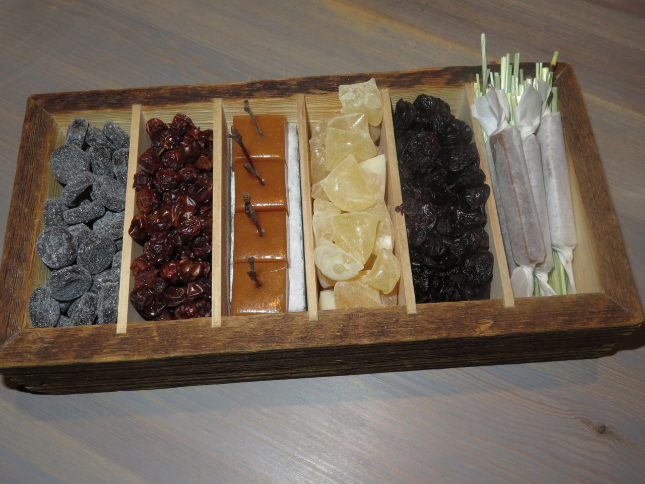 A wooden box filled with tar pastilles, dried rowanberries, smoked caramel, meadowsweet candy, dried black currants, sunflower seed nougat