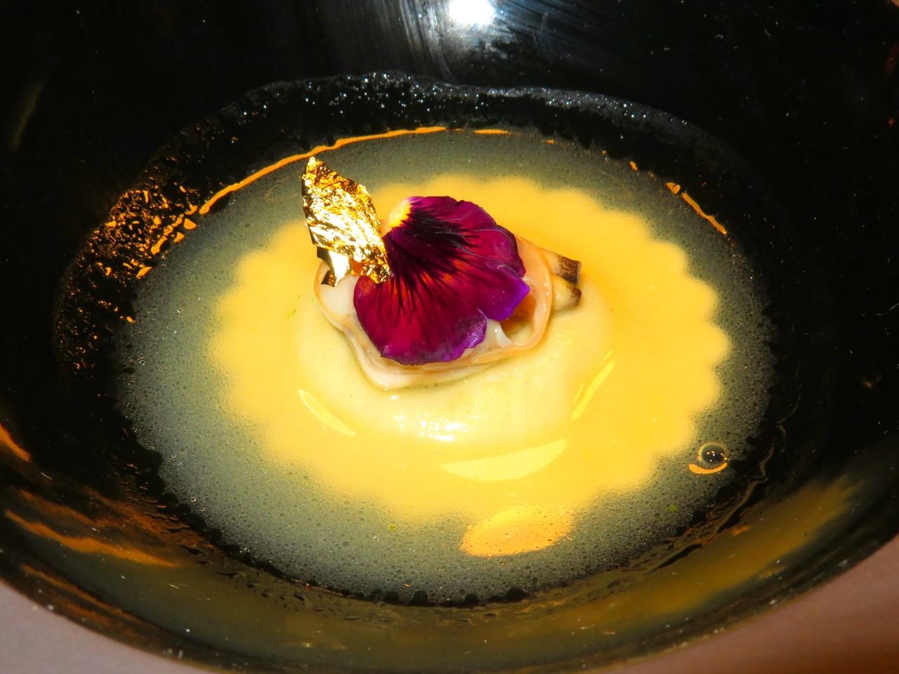 Raviolo de coentros com consommé de amêijoa