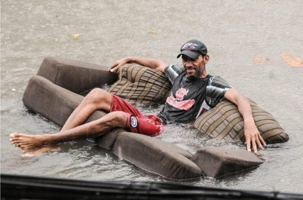 12dez2013---homem-usa-sofa-para-flutuar-em-rua-ala